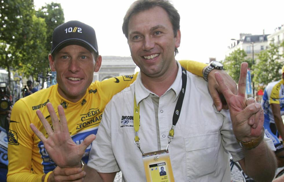 SJU TRIUMFER: Johan Bruyneel holder opp sju fingre, etter Lance Armstrongs sjuende sammenlagttrumf i Tour de France i 2005. Om Armstrong blir funnet skyldig i dopingbruk, risikerer han å miste dem alle. Foto: (AP Photo/Alessandro Trovati, File)