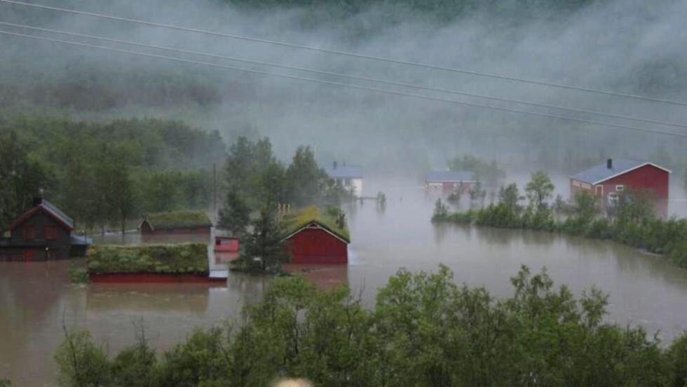 STORFLOM: Det ble dramatisk i går da ekteparet Bjerknes måtte heises opp fra verandaen på gården i Kirkesdalen i Indre Troms. Bjerknes-gården er det hvite huset i bakgrunnen. Foto: Heidi Bjerknes