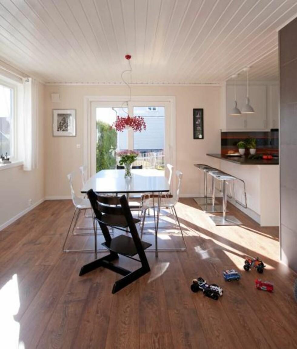 BEVISSTE LINJER: Gulvplankene, i dette tilfellet enstavslaminat fra Pergo, er lagt i rommets lengderetning og bidrar til at blikket dras mot lyset. Spisebord og stoler fra Living. Den røde pendelen SuperLeaves er fra Furtex agenturer, mens pendlene over kjøkkenøya er fra Pur Norsk. Foto: Espen Grønli