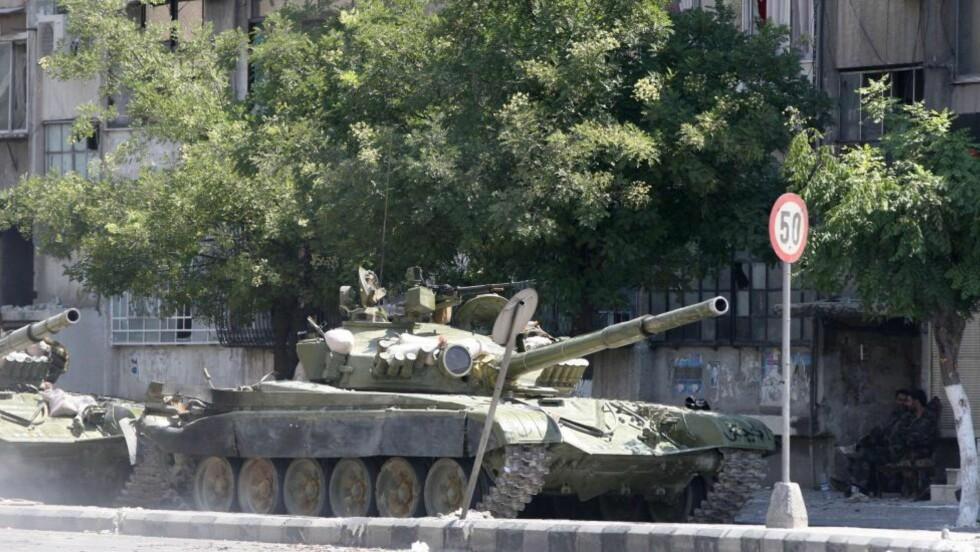 Å RENSKE: På dette viset slåss regimet til president Bashar al-Assad mot sine egne innbyggere. Her ruller stridsvogner inn i bydelen al-Midan i Damaskus, som regjeringsstyrkene har gjenerobret fra opprørerne. Statlig fjernsyn sier myndighetene har «rensket» bydelen for «terrorister». Foto: AFP / LOUAI BESHARA