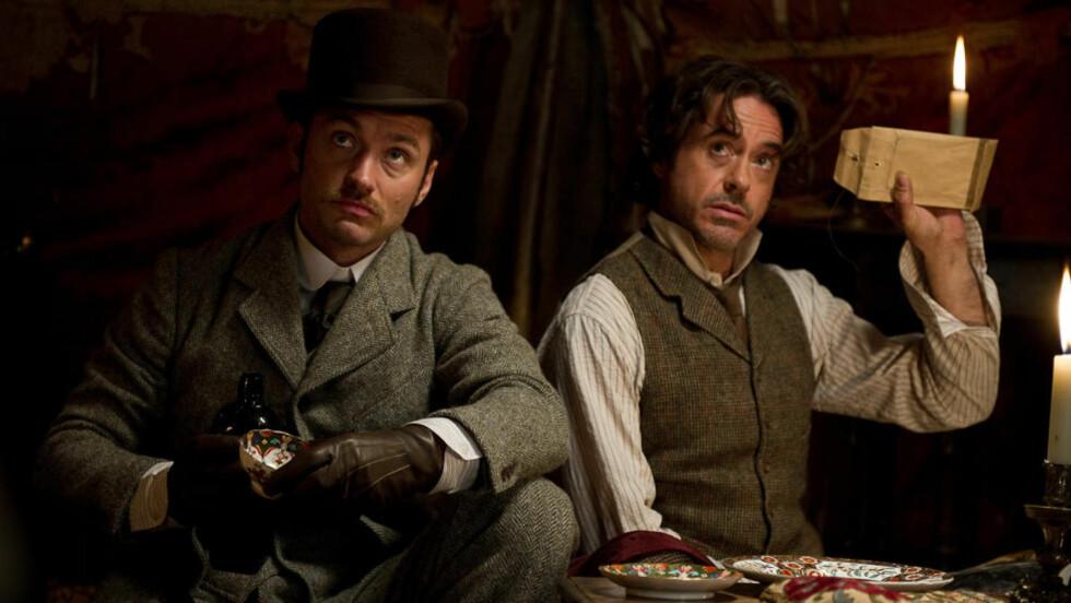 EROTISK FORHOLD? Det var mindre hett mellom Dr. Watson (Hugh Law) og Sherlock Holmes (Robert Downey Jr) i den siste Sherlock Holmes-filmen, enn i boka som nå kommer ut på forlaget Total-E-Bound. Foto: FILMWEB