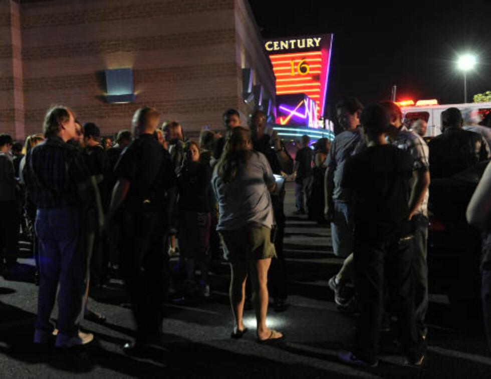 MINST 14 DREPT: Folk har samlet seg utenfor kinoen etter skyteepisoden. AP Photo/Karl Gehring, The Denver Post