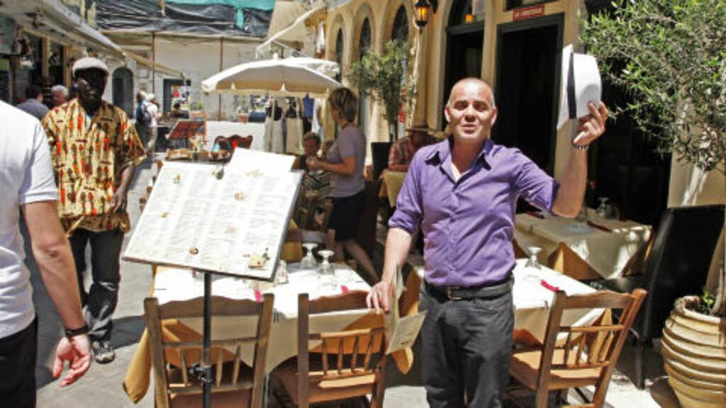 GATELIV: Den gamle bydelen i Korfu by er både koselig og spennende.Kelner Nikos Averinos løfter på hatten og hilser spisegjestene velkommen. Foto: EIVIND PEDERSEN