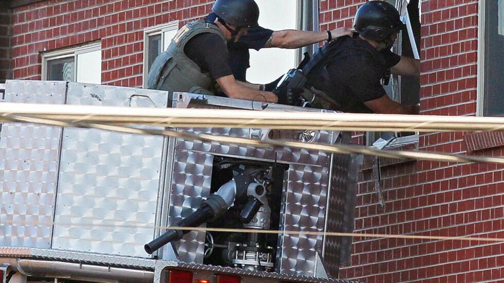 BEREDSKAPSTROPP: Her bruker  tungt bevæpnede politimannskaper et videokamera for å se inn i leiligheten til den pågrepne 24-åringen. Foto: Ed Andrieski / AP