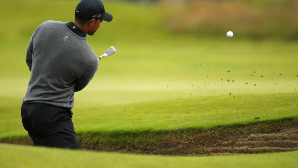 LEKKERT: Woods var i trøbbel nede i en bunker på siste hull. Et chipslag reddet likevel en birdie for Woods da de fleste trodde han måtte avslutte runden med en bogey. Foto: REUTERS/Brian Snyder