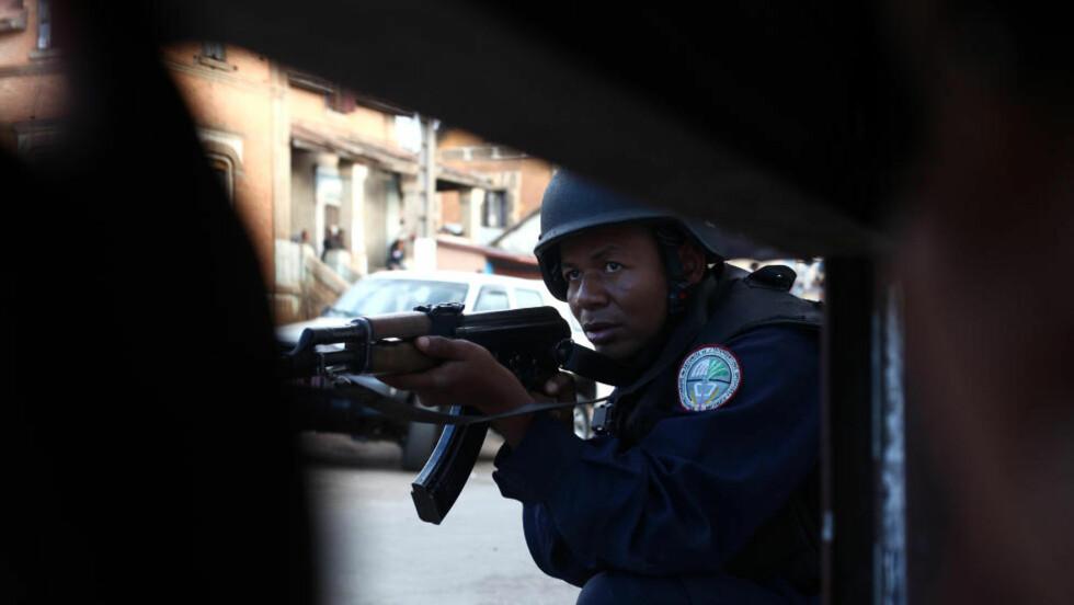 MYTTERI: En politimann tar oppstilling og er i beredskap etter at flere soldater gikk amok i en militærleir. Foto: AFP