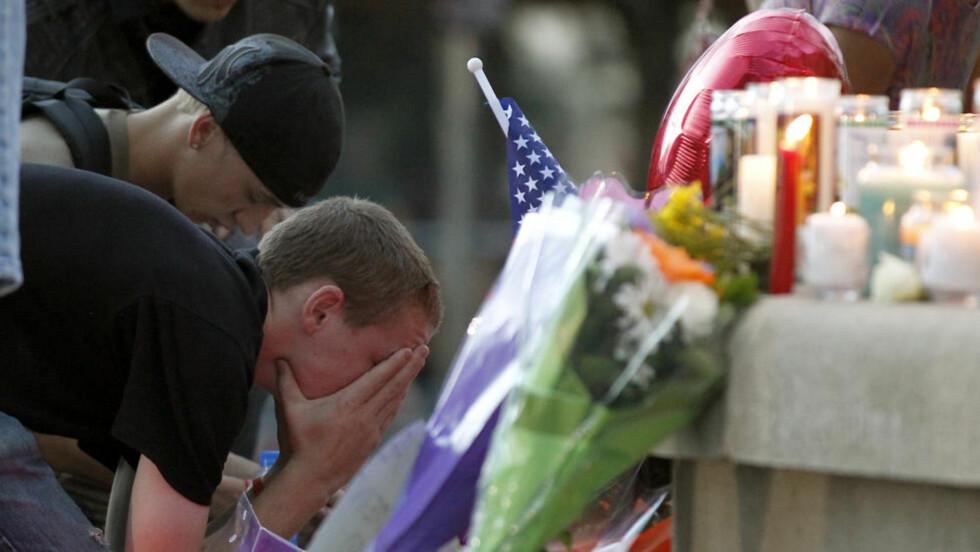 SØRGER: : Folk i byen Aurora i Denver sørger over de døde søndag. Foto: AP Photo/Alex Brandon