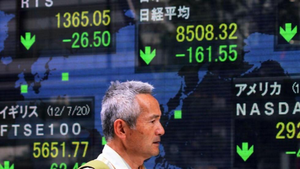 KRISE : En mann går forbi en tavle som viser akskjekursene i Tokyo. Også Tokyo-børsen gikk nedover etter nye bekymringer for Spanias evne til å takle bankkrisen. Foto: Yoshikazu Tsuno/AFP/NTB Scanpix