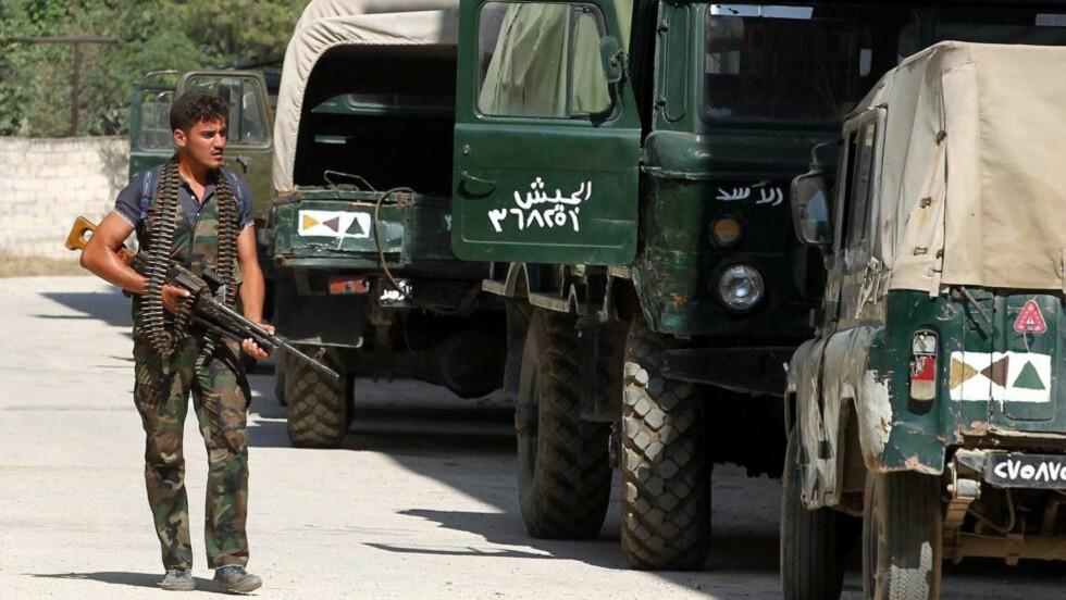 VENTER PÅ DET STORE SLAGET: En syrisk opprørssoldat på patrulje etter at opprørere okkuperte en militærbase i nærheten av Aleppo i Syria 26. juli i år. Det er ventet harde kamper i byen den nærmeste tida. Slaget om Aleppo anses som det viktigste så lang i konflikten. Nå kommer det fram at libyske opprørsstyrker har ankommet Syria for å bistå i kampene. Foto: EPA/SINAN GUL