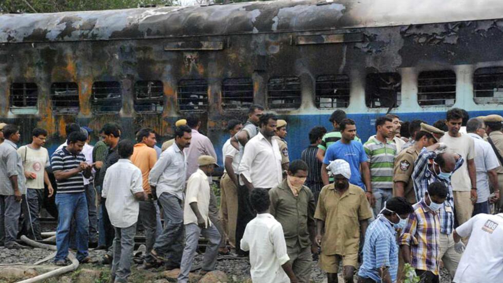 BRANN: Her inspiserer jernbanearbeidere og representanter for myndighetene de utbrente togvognene. Foto: AP Photo/NTBScanpix