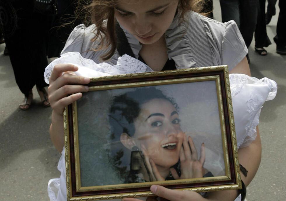 UTØYA-OFFER: En sørgende jente holder portrettet av Tamta Liparteliani, som ble drept av Anders Behring Breivik 22. juli i fjor. Foto: Scanpix /AP / Shakh Aivazov
