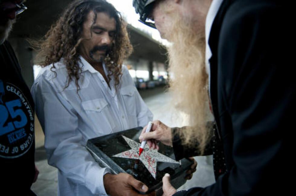 WALK OF FAME: Da ZZ Top onsdag kveld ankom Norge for å spille på Notodden Blues Festival, signerte de det som blir første stein i festivalens egen Walk of Fame. Manager Pablo Gamblo holder steinen, og Billy Gibbons signerer. Foto: Benjamin A. Ward / Dagbladet