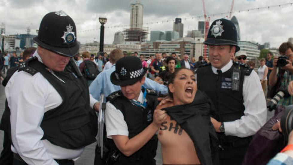 PROTEST: En kvinne blir ført bort av politiet mens en av tjenestekvinnene prøver å dekke til aktivisten. Foto: AFP