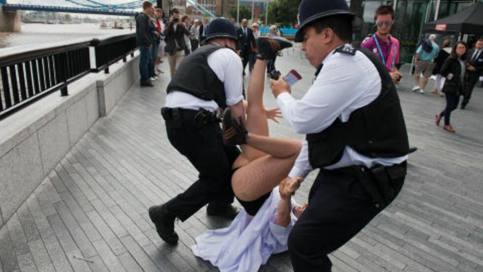 FEBRILSK: En kvinne gjør tydelig motstand da hun blir pågrepet. Foto: AFP