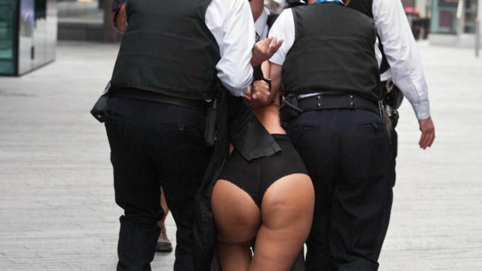 FØRT BORT: Politiet fikk til slutt kontroll på den febrilske kvinnen og førte henne bort. Foto: AFP