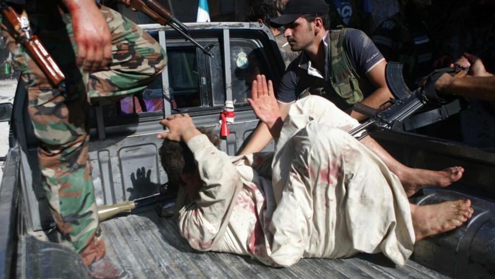 TATT: Assads sikkerhetsstyrker har styrt befolkningen med jernhånd. Her blir en av hans politimenn tatt til fange. Foto: AFP PHOTO/EMIN OZMEN/SABAH PRESS/NTB SCANPIX