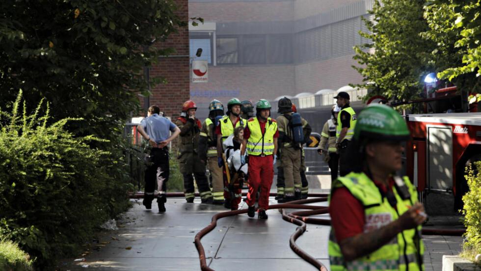 EVAKUERT: Her blir Jorunn Martinsen evakuert fra Hakengata 29 på Tøyen i Oslo, som i dag ettermiddag sto i full brann. Foto: Frank Karlsen / Dagbladet