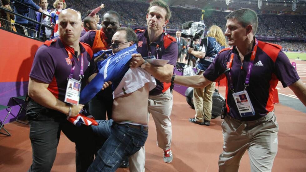 HER ER SYNDEREN: Denne mannen bestemte seg for å kaste en glassflaske inn på banen få sekunder før løperne ble sendt avgårde i 100-meterfinalen i går kveld. Her blir han ført vekk av sikkerhetsvakter. Foto:  REUTERS/Chris Helgren