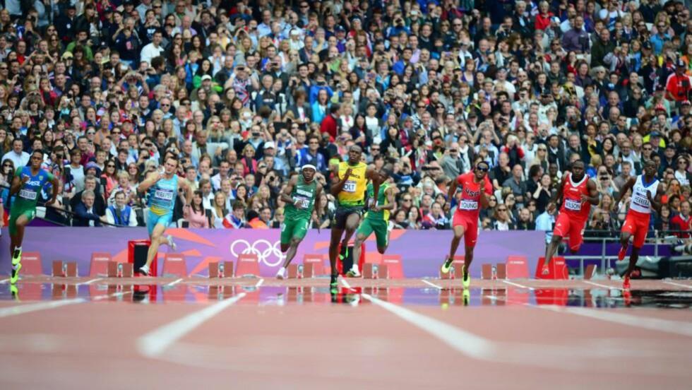 I EGEN KLASSE: Usain Bolt slakket av på gasspedalen allerede i svingen, men hadde null problemer med å holde konkurrentene bak seg. Her omringet av (fra venstre) Aldemir da Silva Junior (Brasil), Vyacheslav Muravyev (Kazakhstan), Noah Akwu (Nigeria), Jidou El Moctar (Mauritius), Isiah Young (USA), Alex Wilson (Sveits) og Jose Carlos Herrera (Mexico). Foto: AFP PHOTO / OLIVIER MORIN