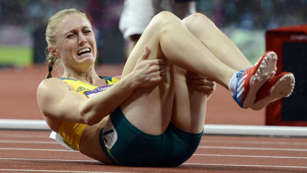 GLEDESFNATT: Sally Pearson våget ikke juble før hun så resultatet på skjermen. Da fikk hun gledesfnatt, kastet seg ned på bakken og lot tårene strømme. Foto: REUTERS/Dylan Martinez