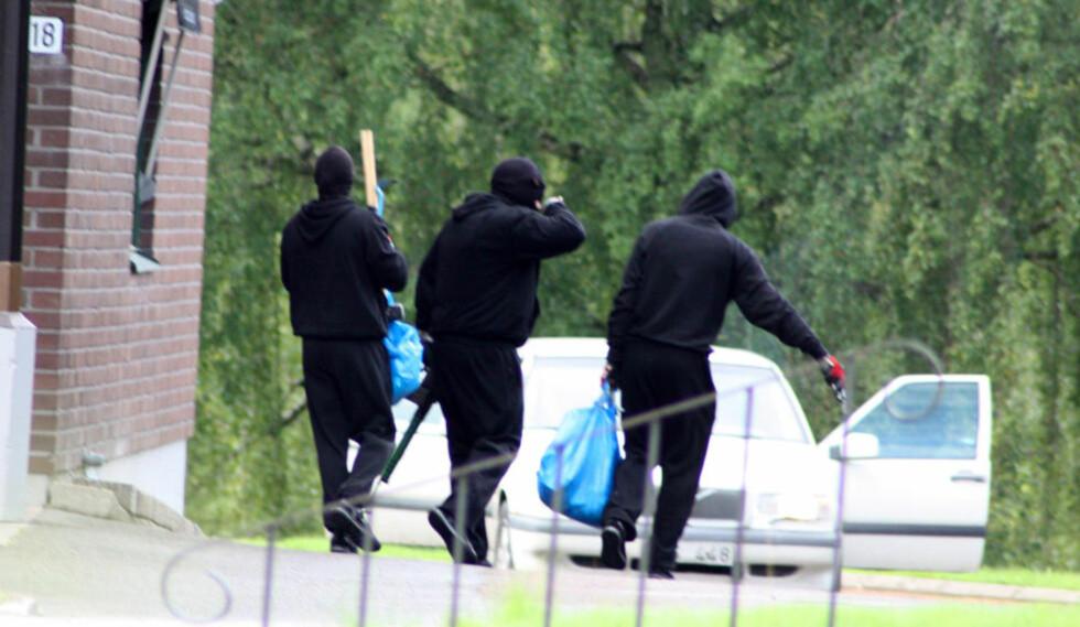 TUNGT BEVÆPNET: De tre ranerne forlater her åstedet, bevæpnet med automatvåpen. De forsvant i Volvoen på bildet. Foto: MORGAN SAHLIN / NTB SCANPIX