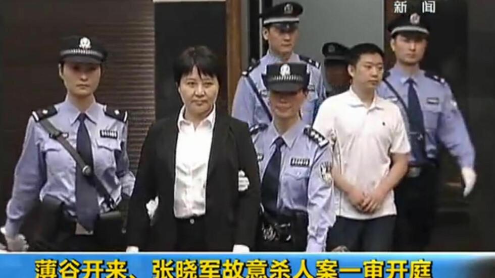 TILTALT: Advokat Gu Kailai, kona til den falne politiske stjerna Bo Xilai, føres inn i retten i Hefei. Sammen med sin medarbeider Zhang Xiaojun er hun tiltalt for gift-mord mot en britisk forretningsmann. Bildet er tatt fra kinesisk fjernsyn. Foto: AFP PHOTO / CCTV