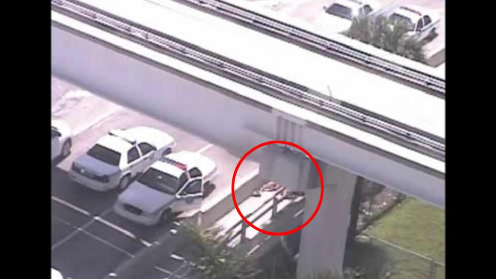 SPISTE AV PERSON: Den nakne mannen nektet å stoppe da politiet advarte ham og begynte å skyte.  Hendelsen skjedde rett ved siden av bygningen avisa The Miami Herald holder til, og bildet er hentet fra deres overvåkningsvideo. Skjermdump: Miamiherald.com
