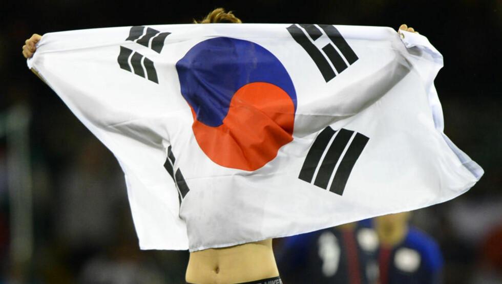 HOLDT OPP SKILT: En sørkoreansk fotballspiller som holdt opp et skilt med et politisk budskap etter bronsekampen mot Japan er uønsket på seierspallen. Spilleren på bildet er ikke personen det er snakk om. Foto: REUTERS/Paul Hackett