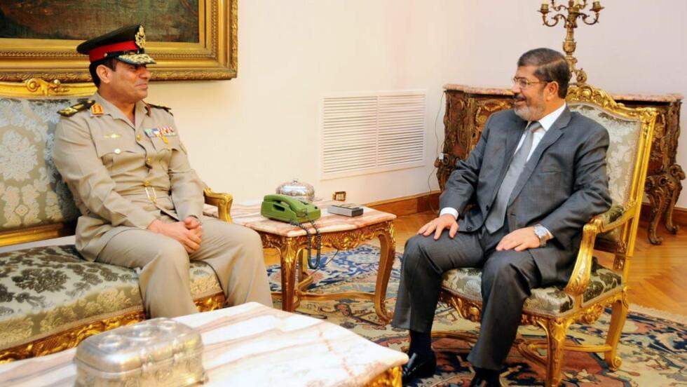 OMMØBLERING:Egypts president, Mohamed Mursi, tar imot sin nye forsvarsminister, Abdel Fattah al-Sissi. Mursi avsatte søndag de to øverste militære lederne. Foto: REUTERS / Presidentens kontor i Egypt