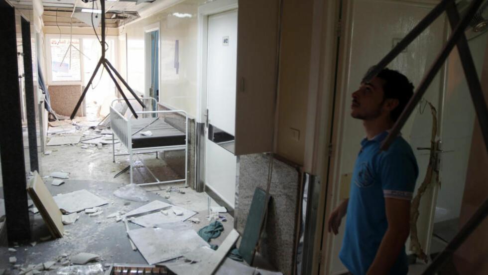 ETTER ANGREP: En ansatt tar skadene i øyesyn ved sjukehuset Dar Al Shifa, etter et angrep fra det syriske flyvåpenet. Regjeringsstyrkene anklages for å bryte krigens folkerett. Foto: Goran Tomasevic / Reuters / NTB Scanpix