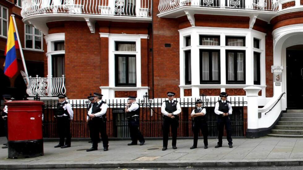 PÅ VAKT:Britiske politimenn står foran den ecuadorianske ambassaden i London torsdag 16. august. I dag ble det klart at Ecuador har innvilget politisk asyl til Julian Assange, bekreftet utenriksministeren Ricardo Patino. Foto: Kerim Okten / EPA
