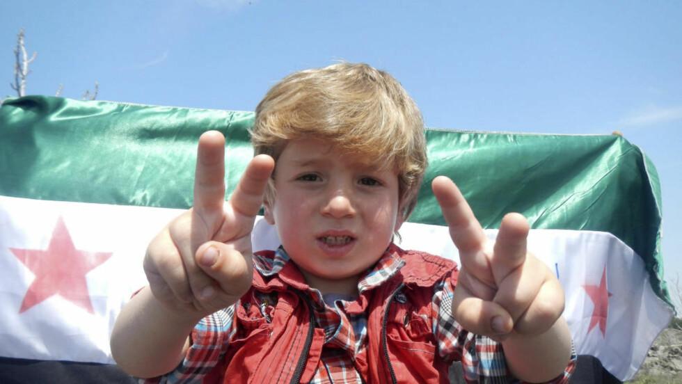 MOT:  En gutt viser v-tegnet i en demonstrasjon langfredag mot Syrias president Bashar Al-Assad i Kafranbel, nær byen Idlib der mange av drapene på sivile skal ha skjedd. FOTO: Raad Al Fares/Shaam News Network/REUTERS/NTB SCANPIX.