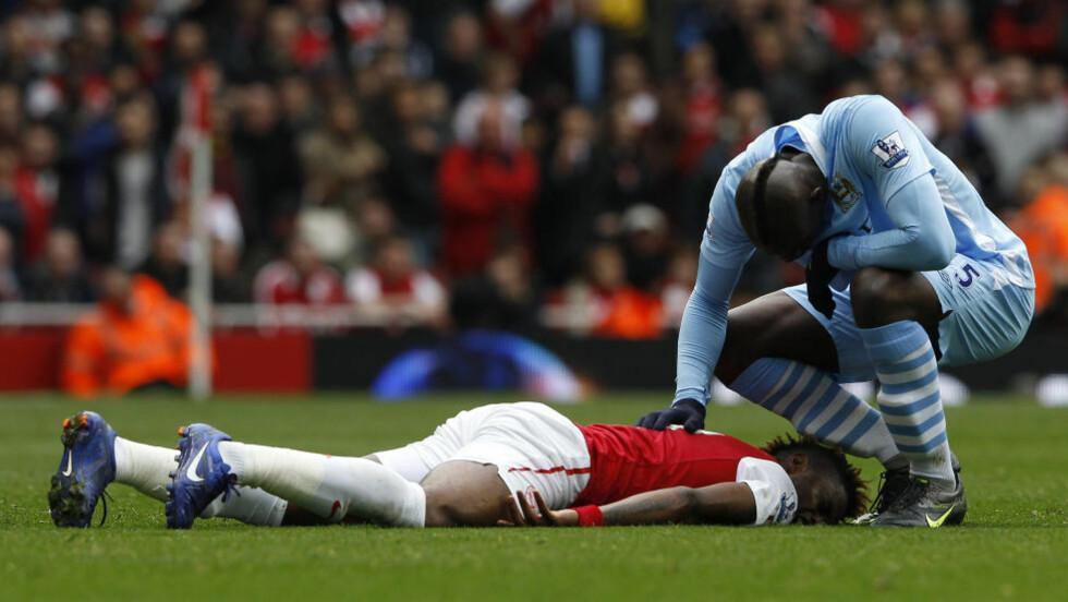 TO RØDE I EN KAMP? Mario Balotelli (t.v) ble utvist mot Arsenal, men kan få enda et rødt kort for taklingen mot Alex Song - som her ligger nede etter at han ble truffet av italienerens knotter. Foto: REUTERS/Stefan Wermuth