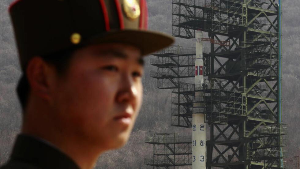 AVDELING HOLDT IKKE: En nord-koreansk soldate holder vakt over raketten som i natt ble skutt ut. Men raketten falt pladask i havet.  REUTERS/Bobby Yip