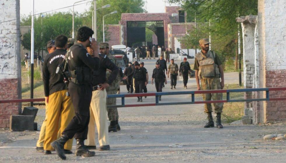 RØMTE: Søndag morgen skal 384 fanger ha fått hjelp fra Pakistans Taliban-bevegelse til å rømme fra dette sentralfengselet i byen Bannu i Pakistan. Her forsøker fengselsvakter å få kontroll over situasjonen etter fangeflukten. FOTO: EPA/RANA ZAHID