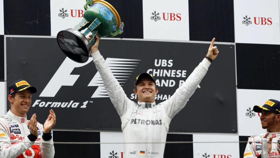 FØRSET BØTTE: Tyskeren Nico Rosberg feirer seieren i Kina Grand Prix i Shanghai. Her sammen med to briter på seierspallen: Nummer to Jenson Button (t.v.) og nummer tre Lewis Hamilton. Foto: Eugene Hoshiko, AP / NTB Scanpix