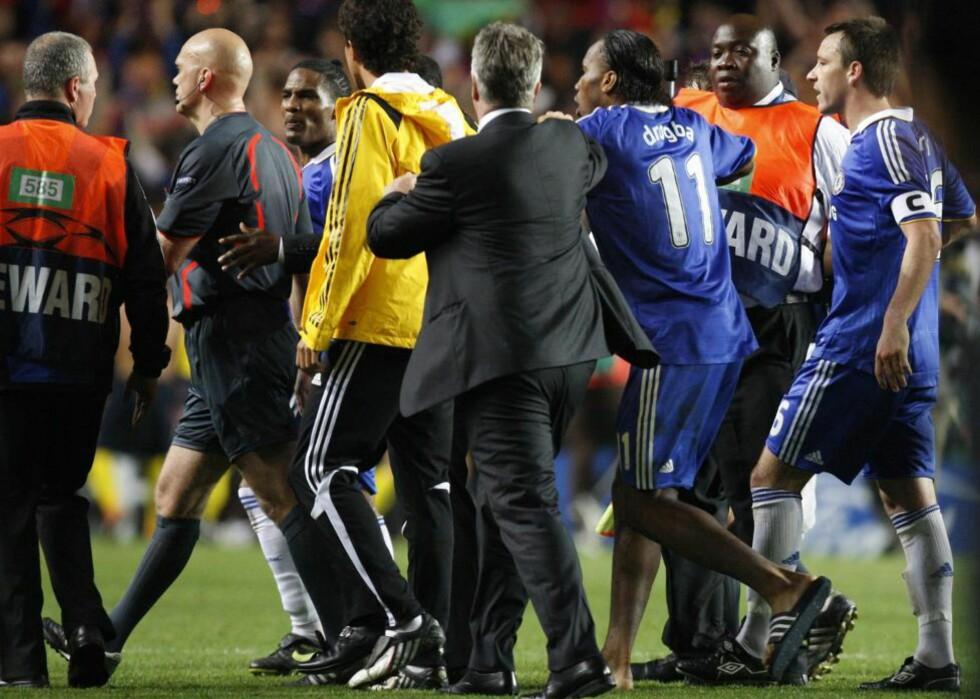 OMRINGET: Tom Henning Øvrebø ble forfulgt av Chelsea-spillere på vei inn i tunnelen etter kampen, og en Didier Drogba i slipperser var den hissigste av dem alle. Foto: (AP Photo/Jon Super)