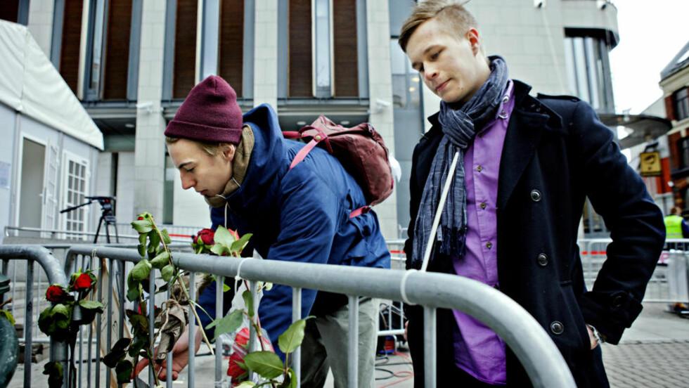 SYMBOLIKK:  Andreas og Emil (t.v) håper flere vil legge ned roser utenfor Tinghuset for å vise at folket fortsatt står samlet og tenker på de rammede etter terroren. Foto:Nina Hansen / Dagbladet
