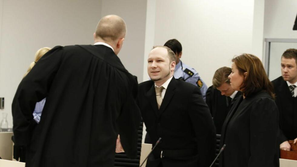 AKTOR OG TILTALT: Anders Behring Breivik hilser på aktor Svein Holden i retten. Stemningen var noe dårligere i dag. Foto: Heiko Junge/NTB Scanpix POOL