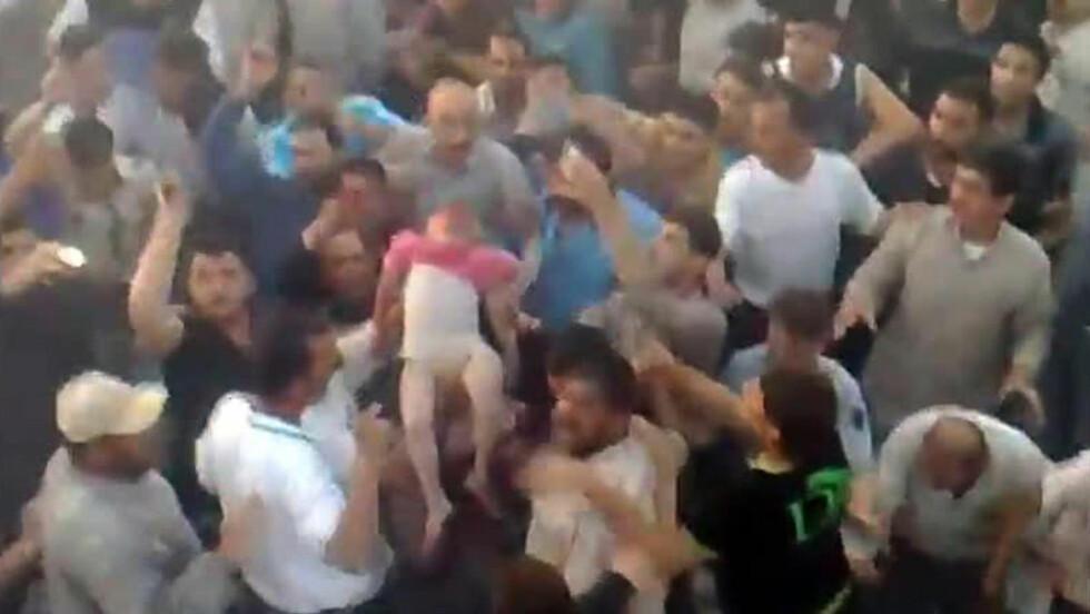 DØDSTALLENE STIGER:  Ifølge syriske aktivister, som la ut videoen som viser disse mennene som trekker døde ut av ruinene, døde mindt 13 barn og 16 kvinner i angrepet mot et området sør i Hama. Foto: AFP PHOTO / YOUTUBE