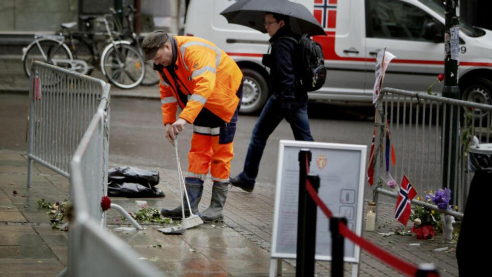 REGNTUNG DAG: ISS fjerner blomster fra rosetoget forrige uke, som ble hengt på gjerdene utenfor tinghuset. Foto: Torbjørn Grønning / Dagbladet