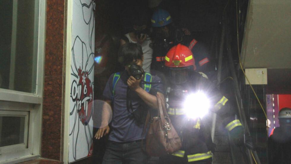BRANN: Brannmenn eskorterer skadde ut av karaokebaren i byen Busan i Sør-Korea, der en brann tok livet av 9 personer. Foto: Reuters/NTBscanpix