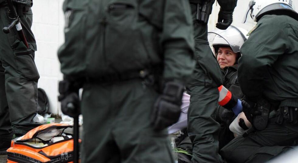 SKADD: Politifolk og medisinsk personell hjelper en skadd kollega i Bonn. Foto: Henning Kaiser/EPA/NTBscanpix