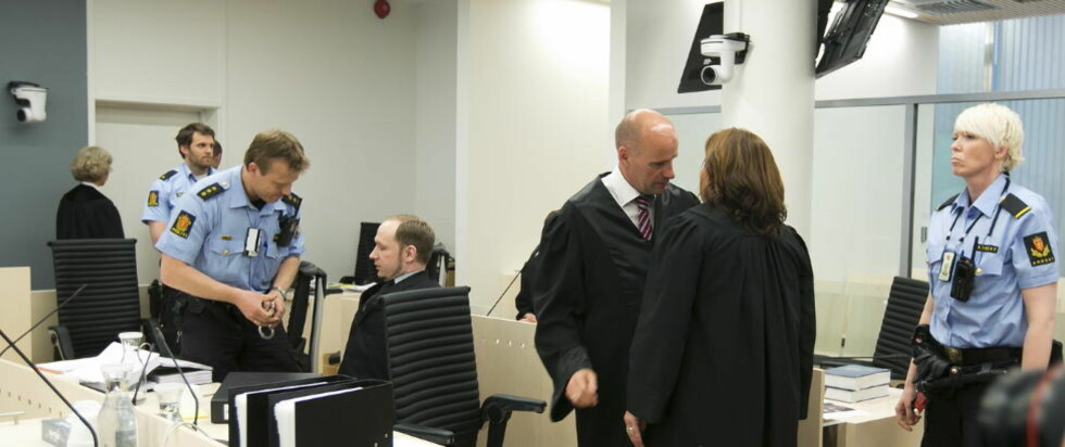 BLE IKKE TRUFFET: - Morder, morder! Du drepte min bror, ropte mannen som kastet en sko mot Anders Behring Breivik i Oslo Tingrett i dag. Mens mannen ble ført ut av politiet reiste flere av tilhørerne i rettssalen seg, og klappet. Andre gråt åpenlyst. Skoen traff ikke Breivik. Foto: HEIKO JUNGE/SCANPIX