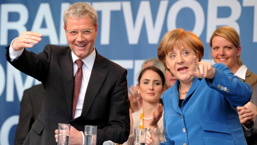 PRØVDE Å HJELPE: Angela Merkel og regjeringspartiet CDUs kandidat i Nordrhein-Westfalen, miljøvernminister Norbert Röttgen, vinker intenst under et valgmøte. Men til ingen nytte, ifølge ferske tall. Foto: AFP / PATRIK STOLLARZ / NTB Scanpix