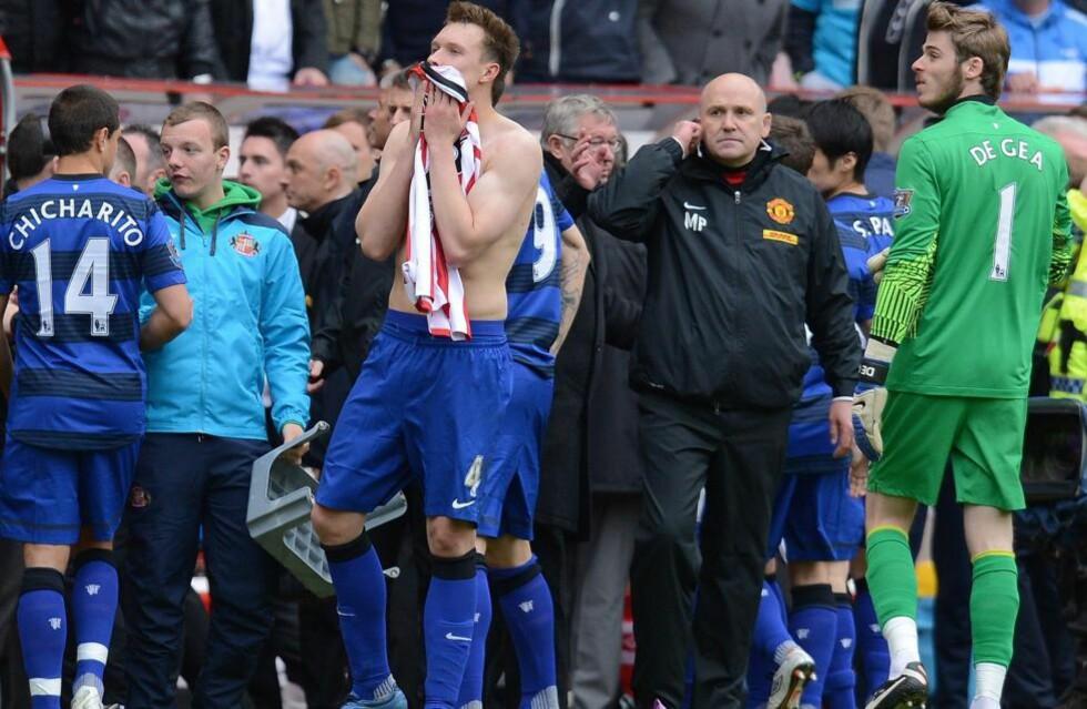 HER FÅR DE BESKJEDEN: Phil Jones og resten av United-laget har nettopp fått beskjeden om Agüeros vinnermål på Etihad. I løpet av tre overtidsminutter snudde City 1-2 til 3-2 - og tok ligagullet. Foto:  AFP PHOTO/ANDREW YATES