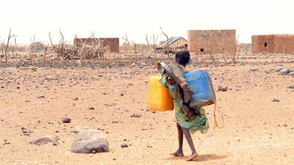 SLÅR ALARM: Amnesty slår alarm om situasjonen i Mali. 15 millioner er rammet av matmangel og hundretusener er drevet på flukt etter opprøret i landet. Mali ble utsatt for et militærkupp 22. mars i år. Her en jente som bærer tomme vannkanner for å fylle dem i landsbyen Katawane. Foto: ABDELHAK SENNA / AFP PHOTO / SCANPIX