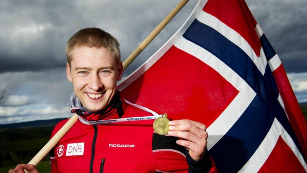 UTKLASSET KONKURRENTENE: Olav Lundanes poserer stolt med gullmedaljen, etter å ha vunnet fredagens langdistanse ett minutt og fem sekunder foran sveitseren Matthias Merz.  Foto: NTB scanpix