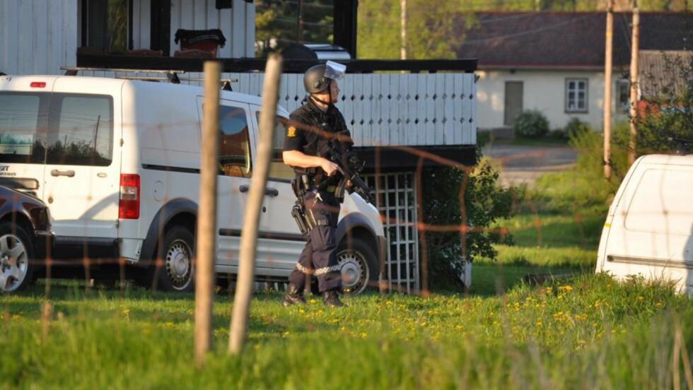 OMRINGET:  Bevæpnet politi har omringet huset mannen har forskanset seg i. Foto: Vegard Aas / Presse 3.0