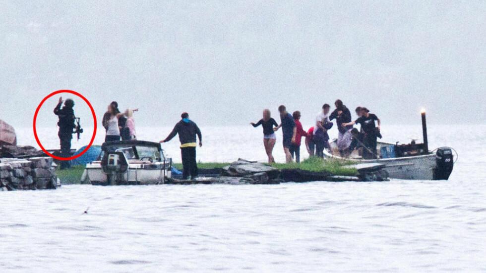 VENTER PÅ LAND: På landsida står en av de to tungt bevæpnede polititjenestemennene og tar imot Eivind Rindal og andre ungdommer som har flyktet fra Utøya med båten «Reiulf». Bildet er tatt cirka klokka 18.15. Foto: Jan Bjerkeli